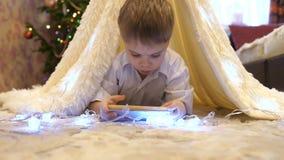 Bambino che gioca smartphone nella stanza dei bambini in una tenda con la luce di Natale Infanzia felice archivi video