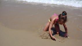 Bambino che gioca in spiaggia della sabbia di mare, bambina sulla linea costiera esotica tropicale del mare stock footage