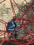Bambino che gioca su un campo da giuoco Fotografia Stock