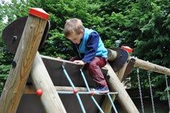 Bambino che gioca su un campo da giuoco Fotografie Stock Libere da Diritti
