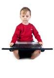 Bambino che gioca sul computer portatile Immagini Stock Libere da Diritti