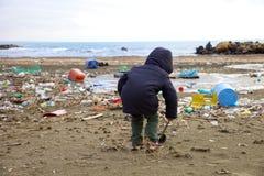 Bambino che gioca sulla spiaggia con il disastro ed il pericolo della sporcizia fotografia stock libera da diritti