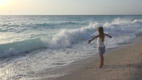 Bambino che gioca sulla spiaggia, ragazza che esamina le onde del mare, bambino che guarda sulla spiaggia fotografia stock