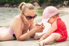 Bambino che gioca sulla spiaggia tropicale con la madre durante le vacanze estive immagine stock libera da diritti