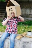 Bambino che gioca in una casa del giocattolo del cartone Fotografia Stock