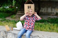 Bambino che gioca in una casa del giocattolo del cartone Fotografie Stock Libere da Diritti