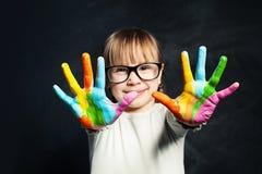 Bambino che gode della sua pittura Ragazza sveglia del bambino con le mani variopinte sul fondo della lavagna dell'aula Arti e is immagine stock