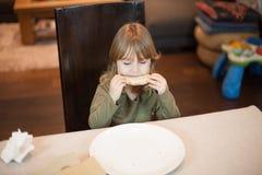 Bambino che gode di una pizza con gli occhi chiusi Fotografia Stock