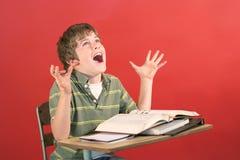 Bambino che grida allo scrittorio Fotografie Stock