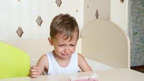 Bambino che grida e che si siede nel suo seggiolone