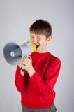 Bambino che grida in megafono su fondo luminoso fotografia stock libera da diritti