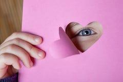 Bambino che guarda attraverso una scheda di forma del cuore Fotografia Stock Libera da Diritti
