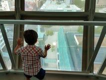 Bambino che guarda fuori finestra dalla torre di osservazione alta Immagine Stock