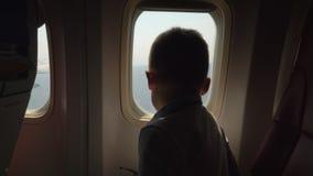 Bambino che guarda tramite la lampadina quando l'aereo sta andando atterrare stock footage