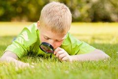 Bambino che guarda tramite la lente d'ingrandimento su terra Immagine Stock