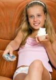 Bambino che guarda TV e che mangia torta immagini stock