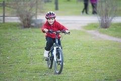 Bambino che guida il suo mountain bike Fotografie Stock Libere da Diritti