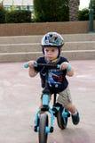 Bambino che guida la sua bicicletta dell'equilibrio Fotografia Stock