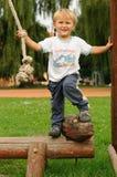 Bambino che ha divertimento sul campo da giuoco Fotografia Stock