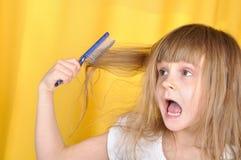 Bambino che ha problema con la spazzolatura dei suoi capelli Fotografia Stock