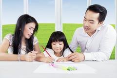 Bambino che impara a casa con i suoi genitori Fotografia Stock