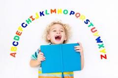 Bambino che impara le lettere dell'alfabeto e di lettura Immagine Stock