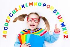 Bambino che impara le lettere dell'alfabeto e di lettura Immagini Stock Libere da Diritti