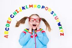 Bambino che impara le lettere dell'alfabeto e di lettura Immagine Stock Libera da Diritti