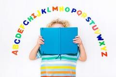 Bambino che impara le lettere dell'alfabeto e di lettura Fotografie Stock