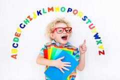 Bambino che impara le lettere dell'alfabeto e di lettura Fotografia Stock