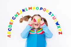 Bambino che impara le lettere dell'alfabeto e di lettura Fotografie Stock Libere da Diritti