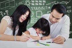 Bambino che impara nella classe con due insegnanti Fotografia Stock Libera da Diritti