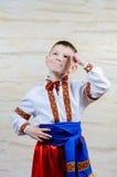 Bambino che indica su mentre portando un costume piega Immagini Stock