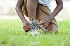 Bambino che indossa le sue scarpe Immagini Stock