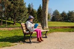 Bambino che legge il libro all'aperto nel parco Immagini Stock Libere da Diritti
