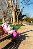 Bambino che legge il libro all'aperto nel parco Immagine Stock