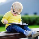 Bambino che legge un libro all'aperto Di nuovo al concetto del banco Fotografie Stock Libere da Diritti