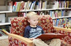 Bambino che legge un libro delle biblioteche su uno strato Fotografie Stock