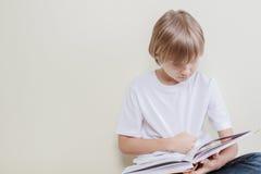 Bambino che legge un libro Istruzione, scuola, concetto di svago Fotografia Stock
