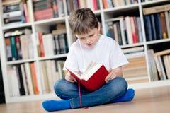 Bambino che legge un libro rosso nella biblioteca Fotografia Stock