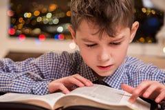 Bambino che legge un libro spesso Fotografia Stock