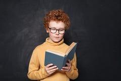 Bambino che legge un libro sul fondo della lavagna Ragazzino sveglio con i capelli dello zenzero fotografia stock libera da diritti