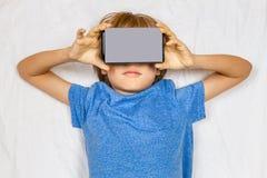 Bambino che liying a letto con 3D la realtà virtuale, vetri del cartone di VR Fotografie Stock Libere da Diritti