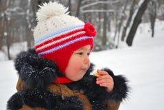 Bambino che mangia biscotto all'esterno nell'orario invernale Fotografia Stock