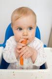 Bambino che mangia carota Immagini Stock