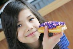 Bambino che mangia ciambella Fotografie Stock
