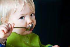Bambino che mangia con il cucchiaio Fotografia Stock