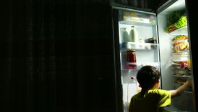 Bambino che mangia davanti al frigorifero nel mezzo della notte