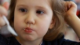 Bambino che mangia dessert e che beve succo nel caffè Ritratto di un bambino che mangia il gelato archivi video