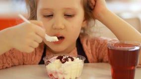 Bambino che mangia dessert e che beve succo nel caffè Ritratto di un bambino che mangia il gelato stock footage